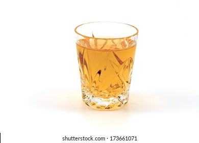 A shot glass of whiskey against a white background