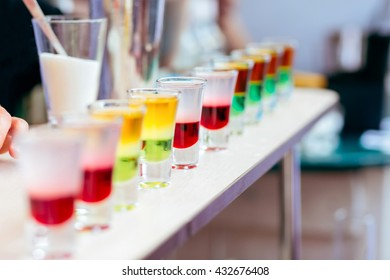 Shot glasses in line in a bar filled with cocktails of various colors. Barman Makes Shots