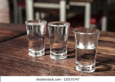 Shot glasses of vodka on a wooden table, addiction to alcohol.
