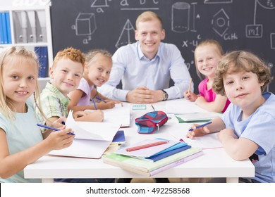 Shot of a goup of children and their teacher sitting around the table and smiling at the camera