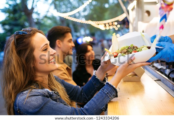 Shot of group of attractive young friends choosing and buying different types of fast food in eat market in the street.