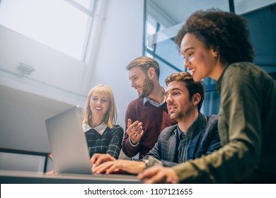 Shot of a group of coworkers discussing something while looking at a laptop computer