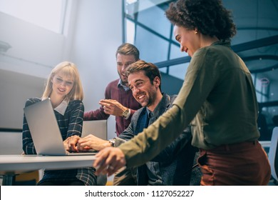 Shot of a group of coworkers looking at a laptop computer