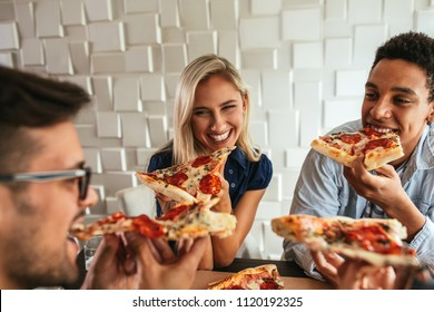 Shot of a group of friends eating pizza in a bar
