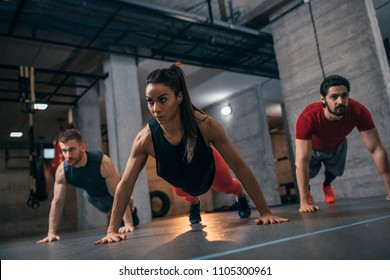 Shot of a group of people doing pushups at the gym