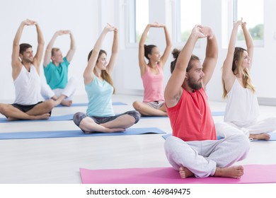 Shot of a group of people sitting with their legs crossed on exercise mats
