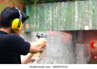 shot gun magazine in hand of man is reflect in flicking after shooting bullet away to the target, effective against weight of gun recoil spring works after shooting by stable action