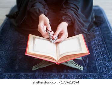Shot hand of Muslim women holding beads  above Quran book teaching from god of Islam - Alloh and praying inside mosque room. She sitting and wearing traditional women clothes - Hijab. Bangkok Thailand