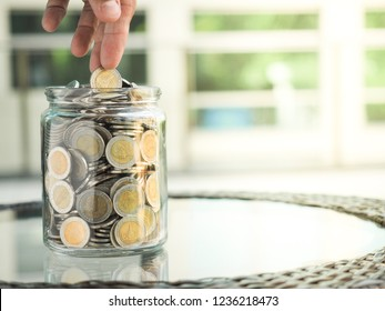 A shot of hand putting or picking the Thai Baht 10 baht coin from the glass jar, refer as saving money