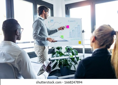 Shot of handsome businessman pointing to whiteboard while explaining to the project to his colleagues on coworking place.