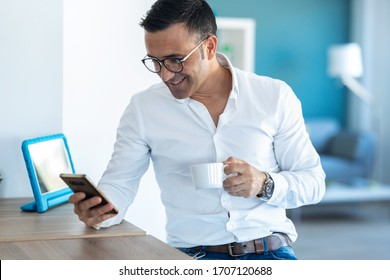 Shot of handsome businessman sending messages with mobile phone while drinking coffee at home.