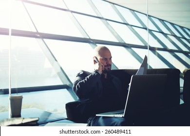 Shot of a handsome businessman talking on a mobile phone while reviewing documents sitting in light modern office interior, business man using laptop computer during coffee time, flare light