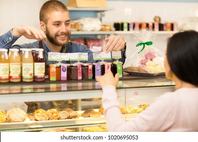 Shot of a handsome cheerful young male shop assistant smiling joyfully talking to his female customer at the confectionery pastry bakery store helping choosing consultant occupation job lifestyle