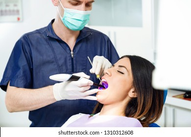 Shot of handsome confident dentist whitening tooth to female patient on dental chair in dental clinic.