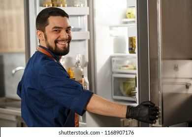 Shot of a handsome happy young male chef smiling to the camera over his shoulder standing in front of an open fridge working at the restaurant kitchen choosing ingredients for the dish.