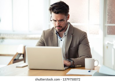 Shot of handsome young business man working with laptop in the office.