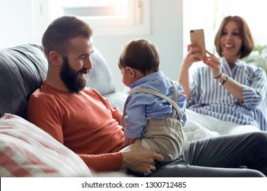 Shot of handsome young father playing with his baby while mother taking photos of them on sofa at home.
