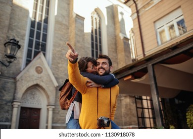 Shot of a handsome young man piggybacking his girlfriend while sightseeing in a foreign city