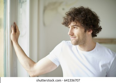 Shot of handsome young man standing at the window and relaxing.
