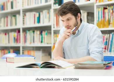 Shot of a handsome young man studying at the college library copyspace student education knowledge academic books writing graduating preparing finals exams smart research project working concept