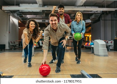 Shot of a handsome young man throwing the bowling ball while his friends are cheering