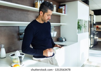 Shot of handsome young man using his mobile phone while drinking coffee in the kitchen at home.