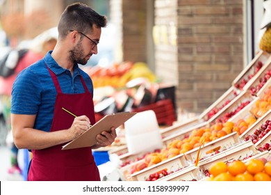 Shot of handsome young salesman doing inventory in health grocery shop.
