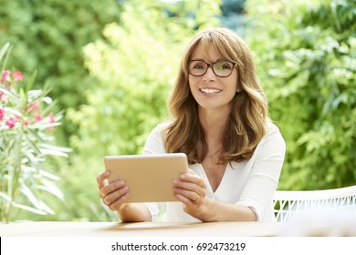 Shot of a happy attractive woman using digital tablet while sitting at home on balcony.