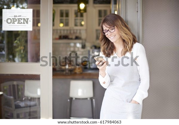 Shot of a happy confident cafe owner standing at doorway and text messaging. Small business.