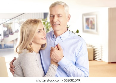 Shot of a happy couple standing at home and embracing each other while looking at camera and smiling.