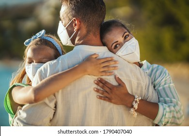 Shot of a happy embraced family with protective N95 mask spending time on the seaside at corona pandemic. They are having self-isolation in nature.