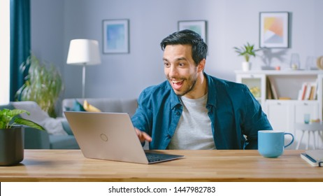 Shot of a Happy and Excited Handsome Man Working on a Laptop. Freelances Working from His Living Room Has Stroke of Luck and Wins Big.