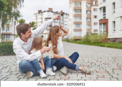 Shot of a happy family looking at their new home. Young couple and their child sitting on the ground near new apartment building copyspace. Family moving to a new home smiling cheerfully outdoors