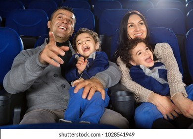 Shot of a happy loving family enjoying watching a comedy or cartoon at the cinema laughing cheerfully parents watching movies with their two twins sons love entertainment bonding parenting childhood.