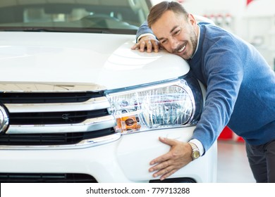 Shot of a happy mature man embracing his new car smiling to the camera cheerfully copyspace emotions expressive consumerism buying dealership showroom vehicle automotive industry