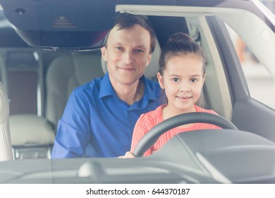Shot of a happy mature man sitting in a car with his cute little daughter smiling together to the camera copyspace parenting happiness lifestyle safety children kids childhood family vehicle transport