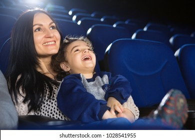 Shot of a happy mature woman smiling enjoying watching a funny cartoon with her little son at the cinema copyspace family parenthood motherhood emotions laughing kids children enjoyment.