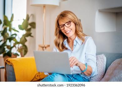 Aufnahmen einer glücklichen Frau mittleren Alters mit ihrem Laptop auf dem Sofa zu Hause.