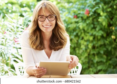 Shot of a happy middle aged woman using digital tablet while relaxing outdoor.