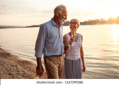 Shot of a happy senior couple drinking champagne by the river