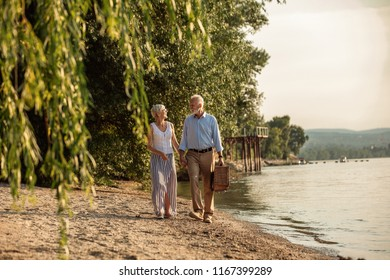 Shot of a happy senior couple going to picnic at the riverbank