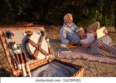 Shot of a happy senior couple having a picnic at the riverbank