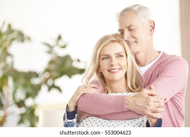 Shot of a happy senior couple standing together. Elderly man hugging her wife from behind while at home in living room.
