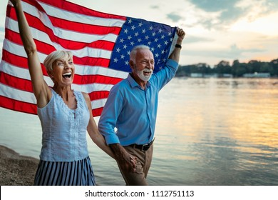 Shot of a happy senior couple walking by the river with an American flag