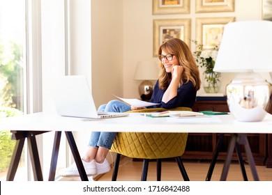 Aufnahmen von glücklich lächelnden Geschäftsfrau mit ihrem Laptop während der Arbeit zu Hause. Heimbüro.
