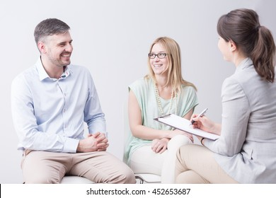 Shot of a happy young couple talking to a young woman with a flipboard