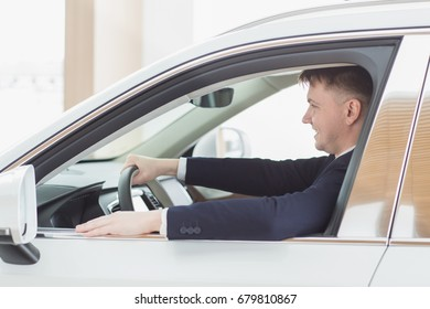 Shot of a happy young handsome man smiling sitting in his newly bought car at the dealership showroom copyspace comfort modern automotive industry business leasing rental owning ownership cars concept