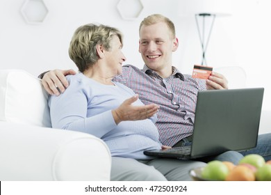 Shot of a happy young man explaining online payments to his grandmother