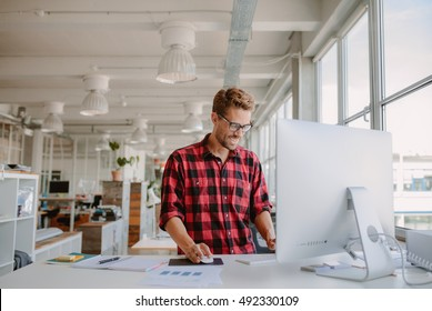 Shot of happy young man working on desktop computer in modern workplace. Young entrepreneur working at start up.
