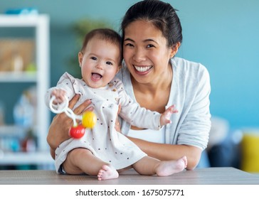 Shot of happy young mother with her baby daughter looking at camera while staying at home.